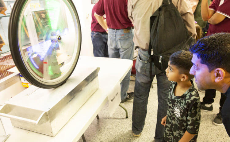 Children peer into a fast-spinning wheel displaying persistence of vision colors and shapes.